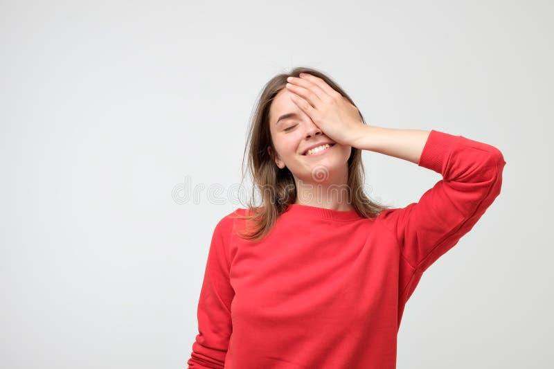 Femme caucasienne heureuse utilisant le chandail rouge souriant et gardant la main sur sa joue photographie stock
