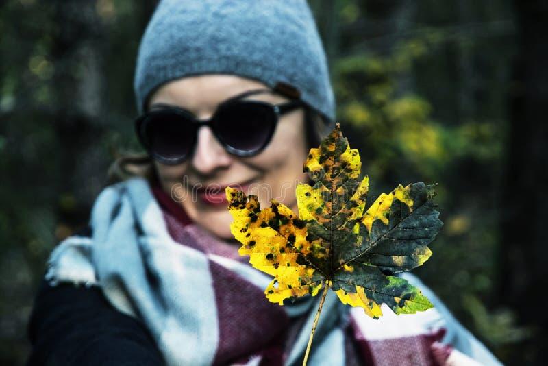 Femme caucasienne joyeuse avec la feuille d'érable colorée en nature d'automne image libre de droits
