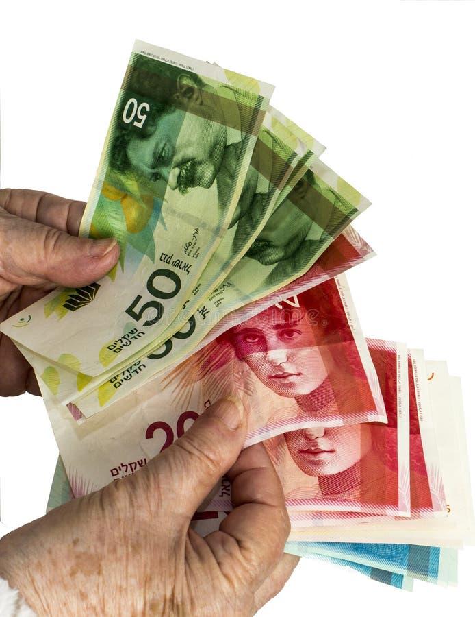 Femme caucasienne pluse âgé comptant les billets de banque israéliens de shekel Isolat images libres de droits