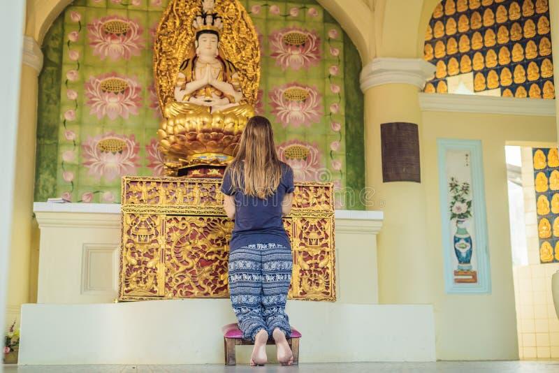 Femme caucasienne priant dans un temple bouddhiste photo stock