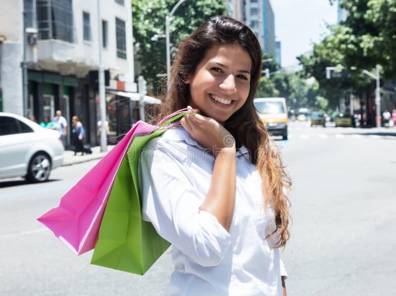 Femme caucasienne riante avec des paniers dans la ville images stock