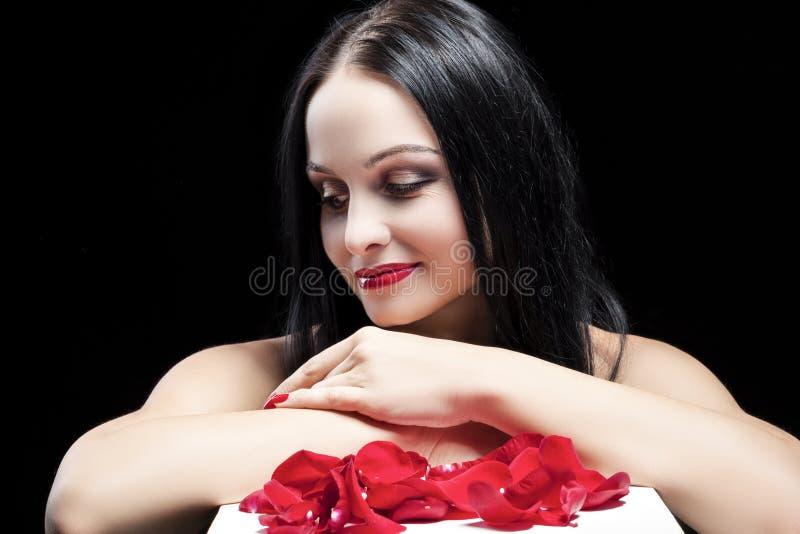 Femme caucasienne semblante sexy de brune posant contre le noir image libre de droits