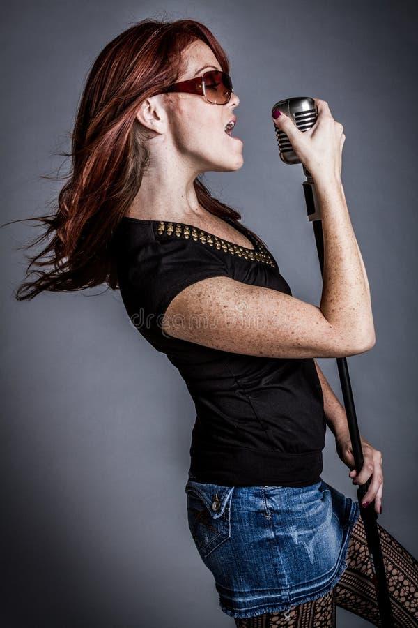 Femme chantant avec le microphone photographie stock libre de droits