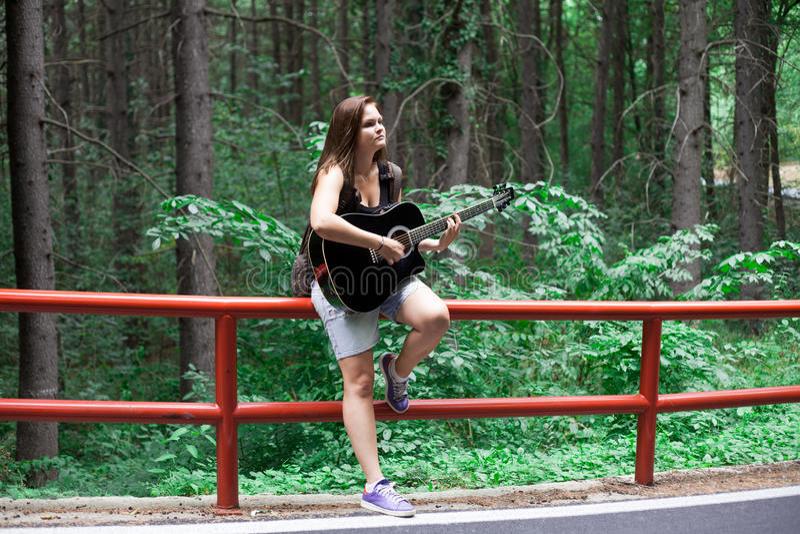 Femme chantant dans une forêt d'un côté de route sur une guitare acoustique noire images stock