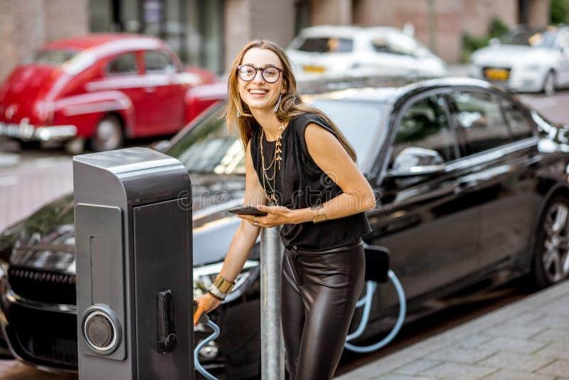 Femme chargeant la voiture électrique dehors image stock