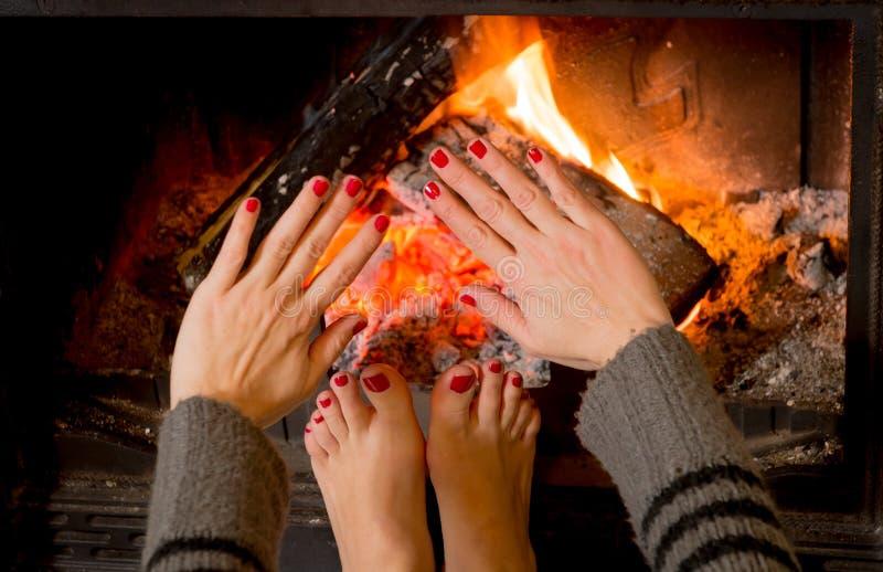 Femme chauffant ses pieds d'ands de mains image libre de droits