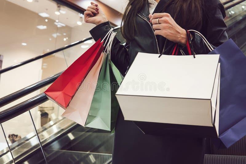 Femme chic de culture avec le tas des sacs à provisions allant vers le bas sur l'escalator Ventes saisonnières et achats femelles images stock