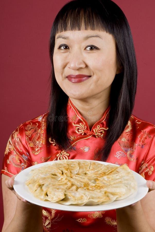 Femme chinois jugeant une plaque pleine des boulettes image libre de droits