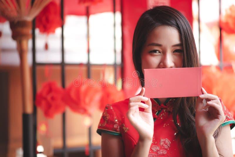 Femme chinoise asiatique heureuse dans la robe rouge traditionnelle de Cheongsam montrant l'enveloppe rouge Ang Pao photo stock