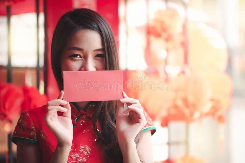 Femme chinoise asiatique heureuse dans la robe rouge traditionnelle montrant l'enveloppe rouge Ang Pao pendant la nouvelle année  photographie stock libre de droits