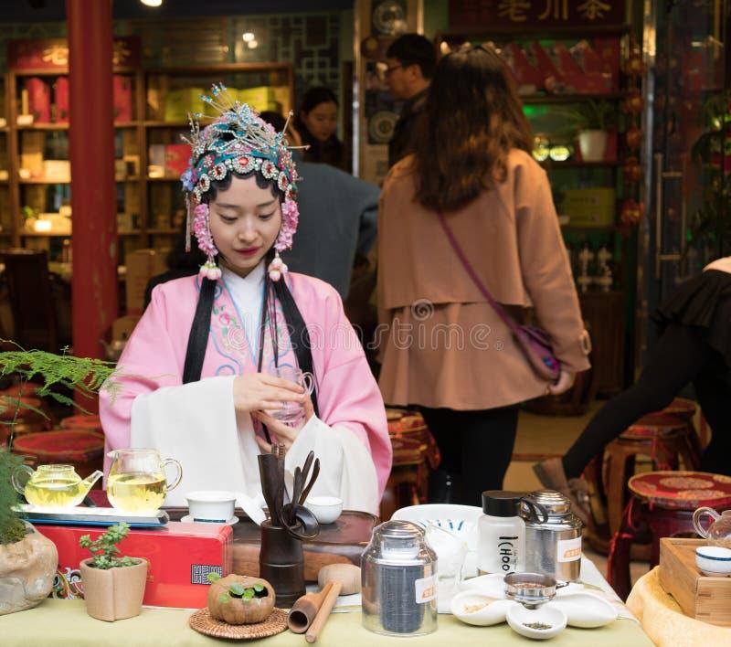 Femme chinoise avec la robe traditionnelle préparant le ceremon de thé vert photo libre de droits
