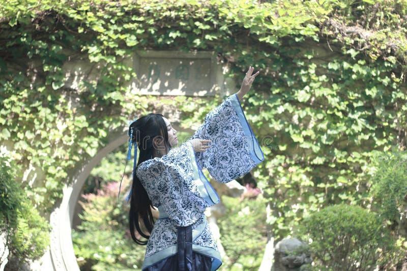 Femme chinoise dans la robe bleue et blanche traditionnelle de Hanfu se tenant au milieu de la belle porte photos stock