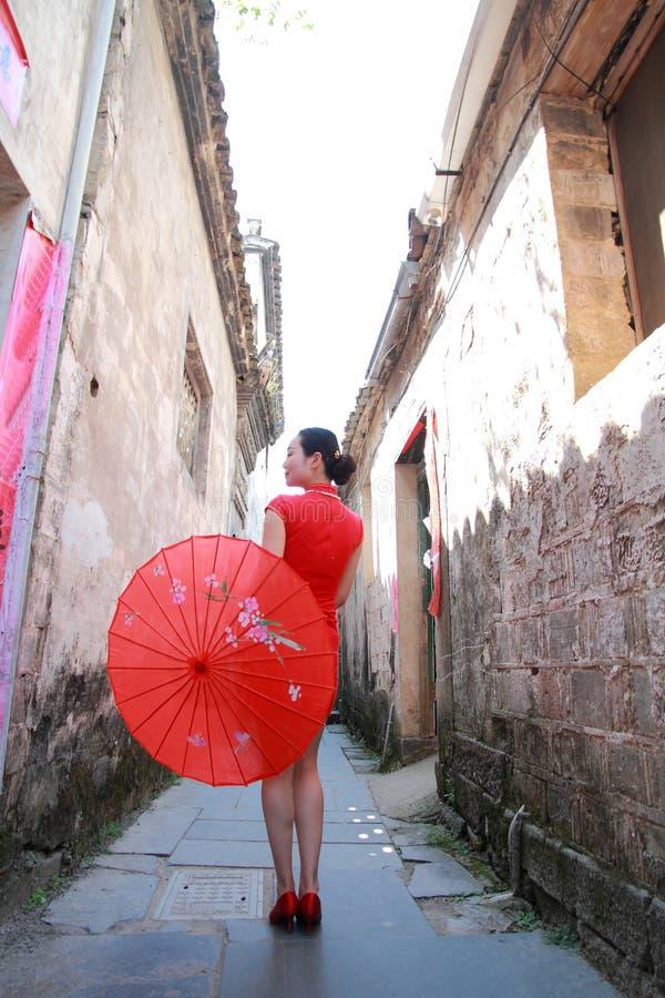 Femme chinoise heureuse dans la promenade rouge de cheongsam dans l'allée images libres de droits