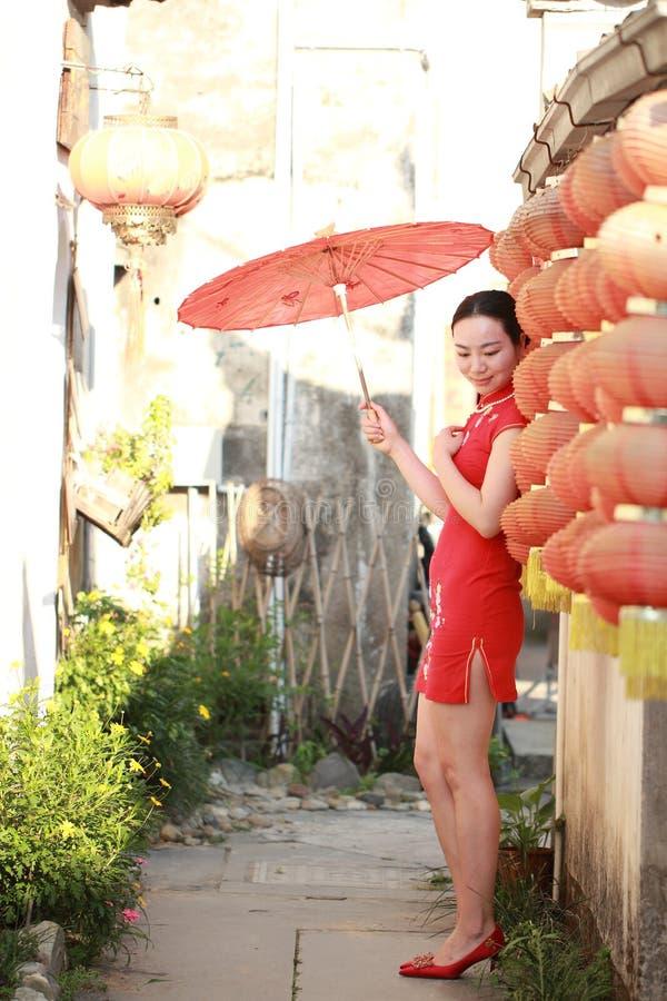 Femme chinoise heureuse dans le cheongsam rouge au jour du mariage traditionnel photographie stock libre de droits