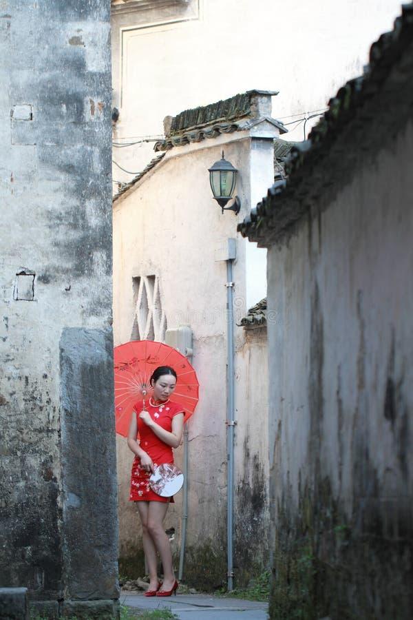 Femme chinoise insouciante dans le cheongsam rouge buvant et lue images stock