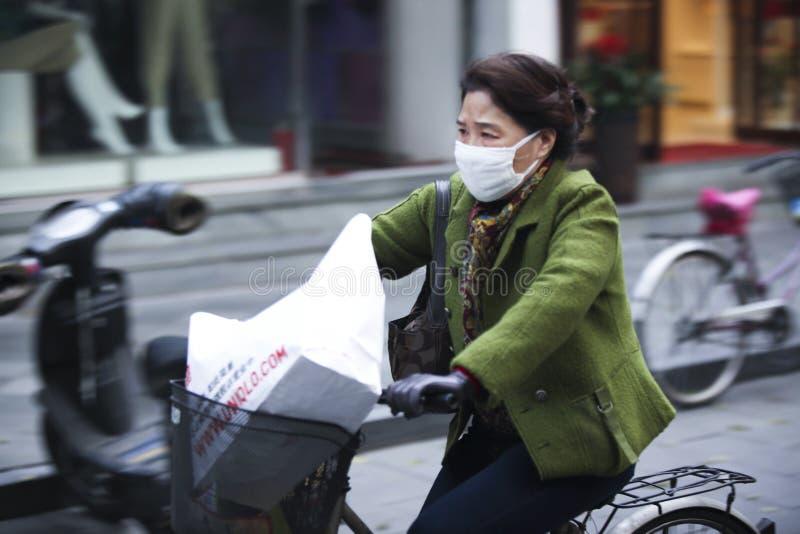 Femme chinoise montant un vélo au-dessus de la pollution de la Chine photographie stock