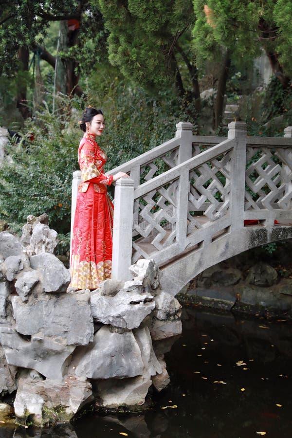 Femme chinoise portant la robe rouge en soie d'une jeune mariée chinoise typique, ornée avec Phoenix d'or et traîner sur le pont photos stock