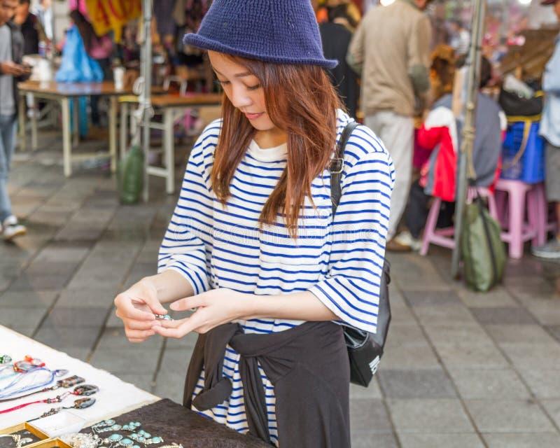 Femme chinoise regardant des bijoux le marché image libre de droits