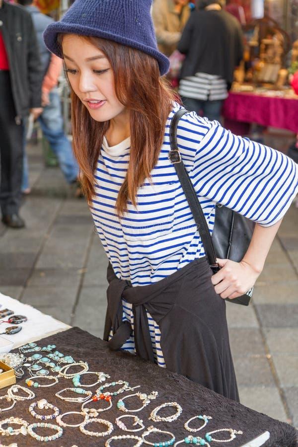 Femme chinoise regardant des bijoux le marché photographie stock
