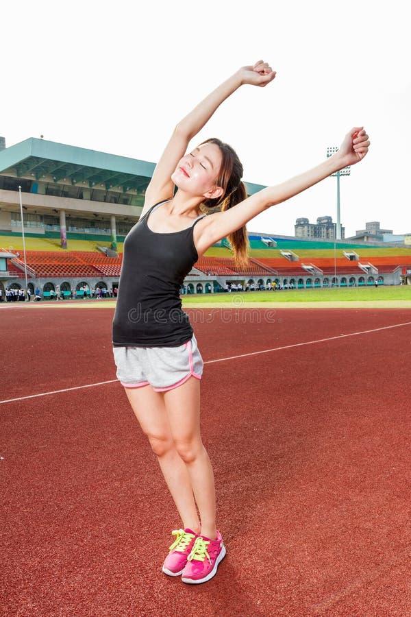 Femme chinoise s'étirant sur la voie au stade photos stock