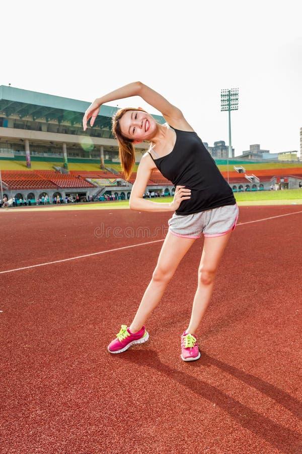 Femme chinoise s'étirant sur la voie au stade image stock