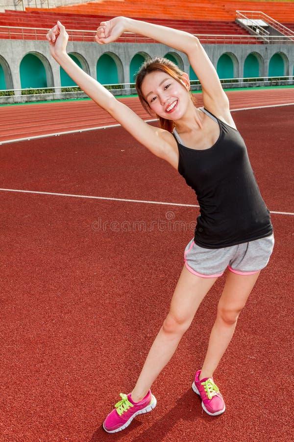 Femme chinoise s'étirant sur la voie au stade images stock
