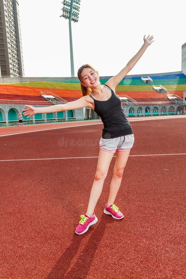 Femme chinoise s'étirant sur la voie au stade image libre de droits