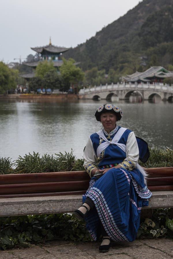 Femme chinoise utilisant un vêtement traditionnel de minorité de Bai se reposant devant Dragon Pool noir dans Lijiang image stock