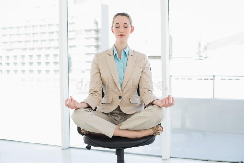 Femme chique attirante s'asseyant en position de lotus sur sa chaise pivotante photo stock