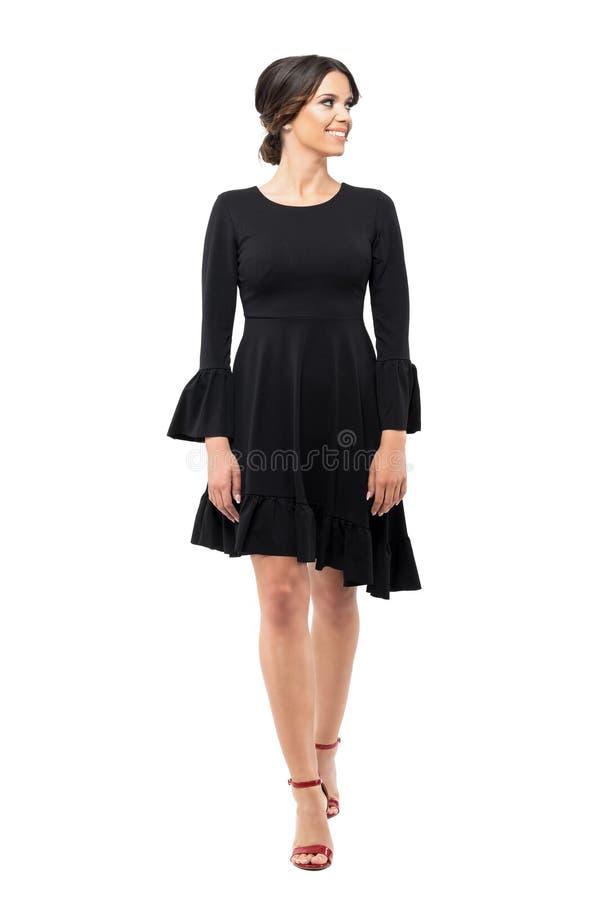 Femme chique de charme heureux dans la robe noire marchant et regardant loin souriante photo libre de droits