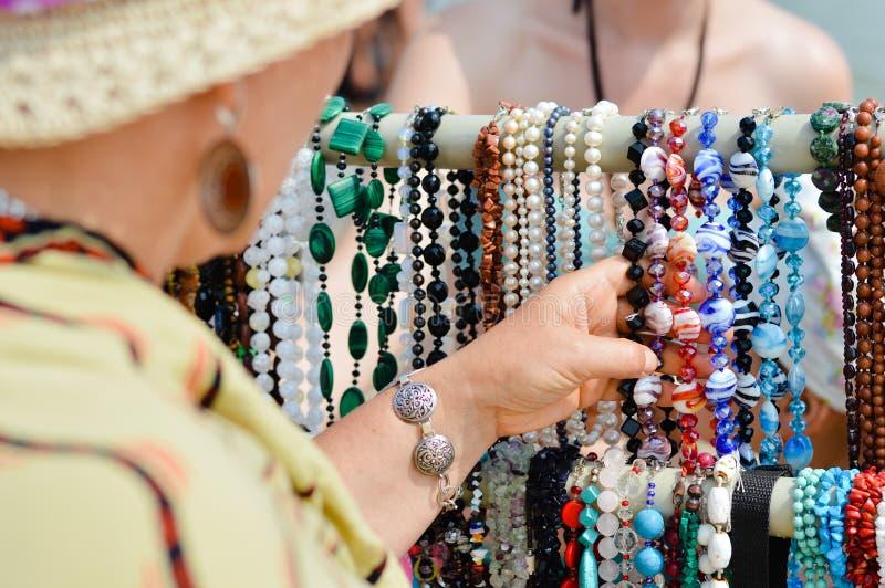 Femme choisissant des bijoux dans la rangée des colliers et des bracelets photo libre de droits
