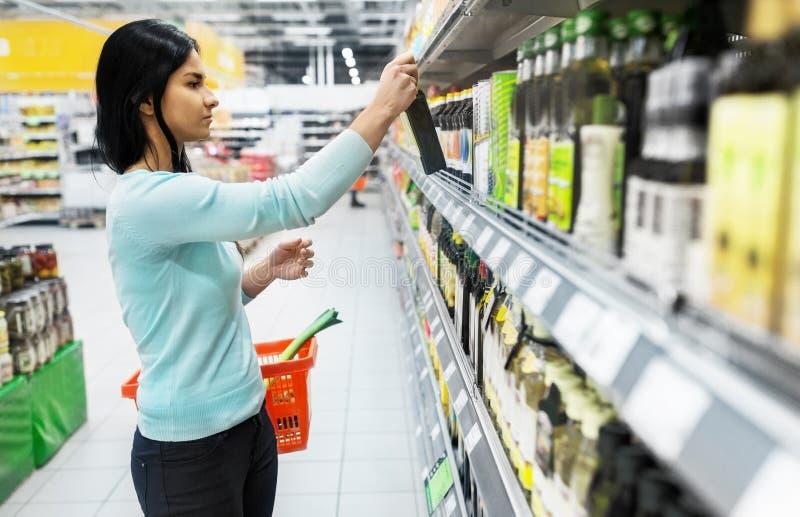 Femme choisissant l'huile d'olive au supermarché ou à l'épicerie images libres de droits