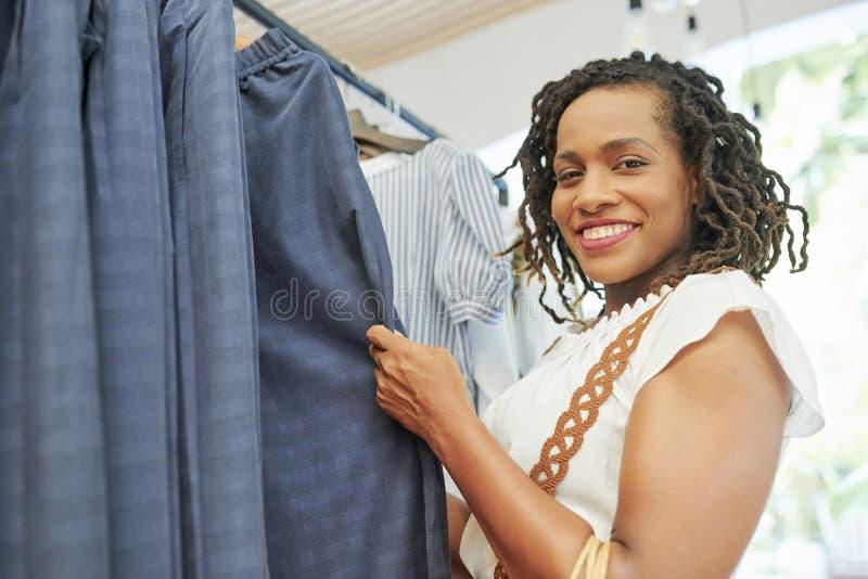 Femme choisissant un costume dans le magasin photographie stock
