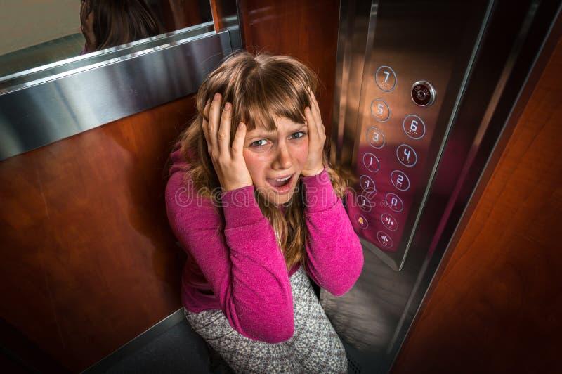 Femme choquée avec la claustrophobie dans l'ascenseur mobile photographie stock