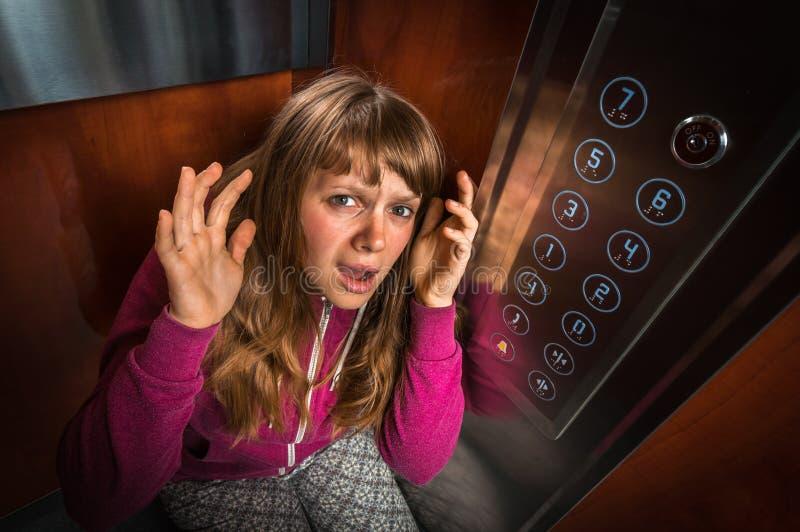 Femme choquée avec la claustrophobie dans l'ascenseur mobile image libre de droits