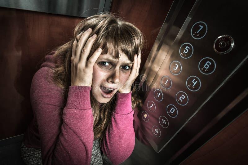 Femme choquée avec la claustrophobie dans l'ascenseur mobile images libres de droits