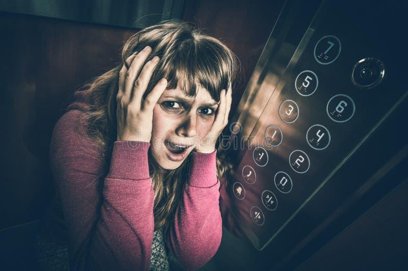 Femme choquée avec la claustrophobie dans l'ascenseur mobile photo stock