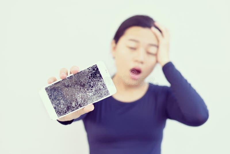 Femme choquée avec un téléphone cassé dans sa main photo stock