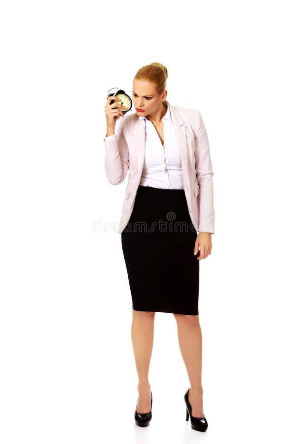 Femme choquée d'affaires écoutant le réveil photos stock