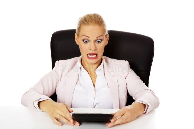 Femme choquée d'affaires s'asseyant derrière le bureau avec la calculatrice photo stock
