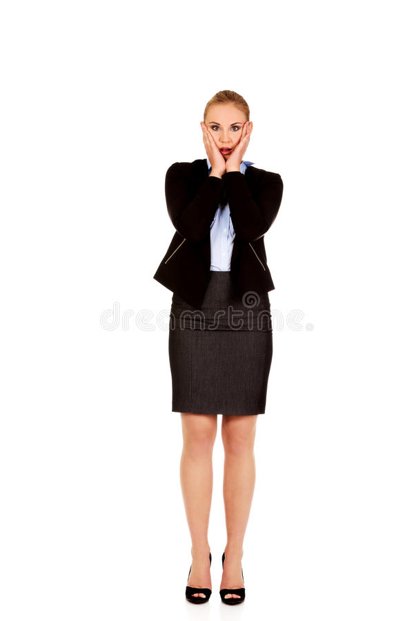 Femme choquée d'affaires tenant des mains sur des joues image stock