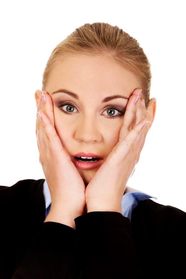Femme choquée d'affaires tenant des mains sur des joues photo libre de droits