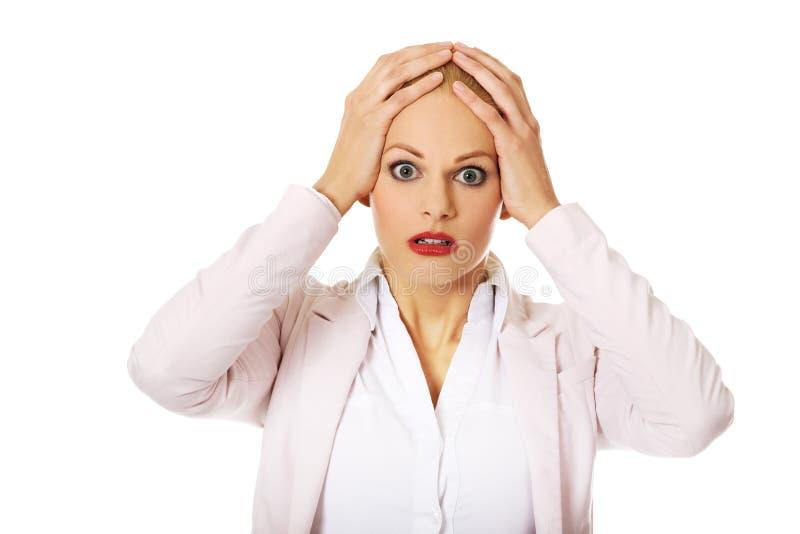 Femme choquée d'affaires tenant des mains sur la tête photo stock