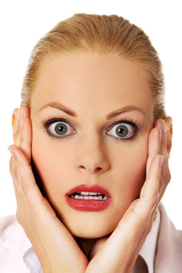 Femme choquée d'affaires tenant des mains sur le menton photo stock