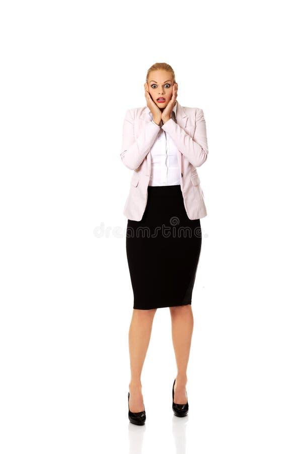 Femme choquée d'affaires tenant des mains sur le menton photographie stock