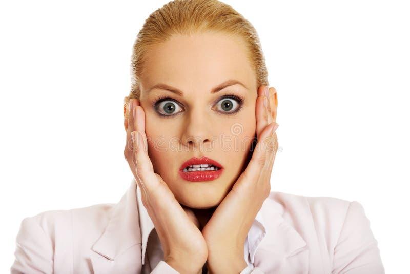 Femme choquée d'affaires tenant des mains sur le menton photographie stock libre de droits