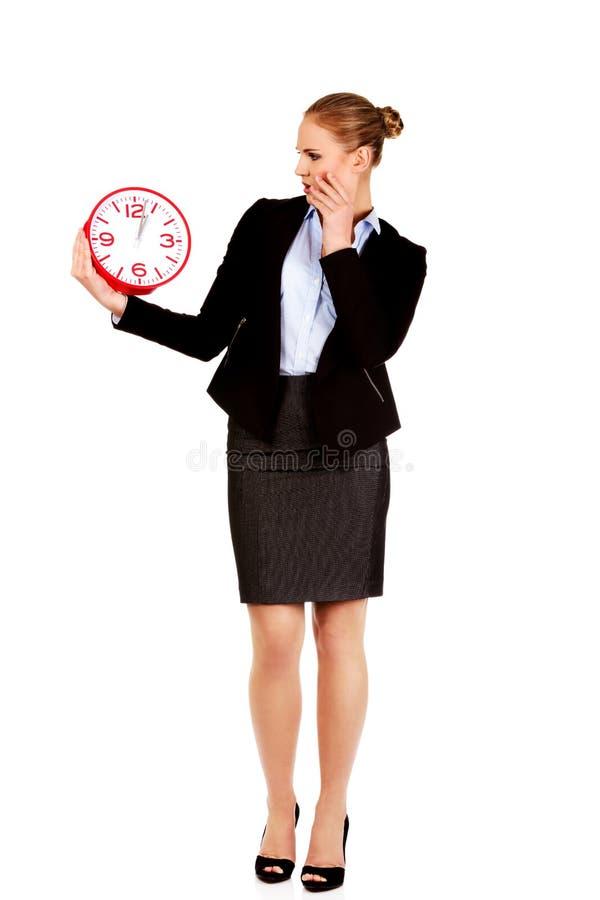 Femme choquée d'affaires tenant l'horloge de bureau photos stock