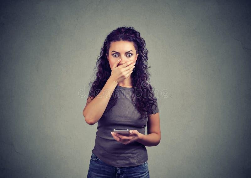 Femme choquée recevant la mauvaise nouvelle au téléphone photo stock