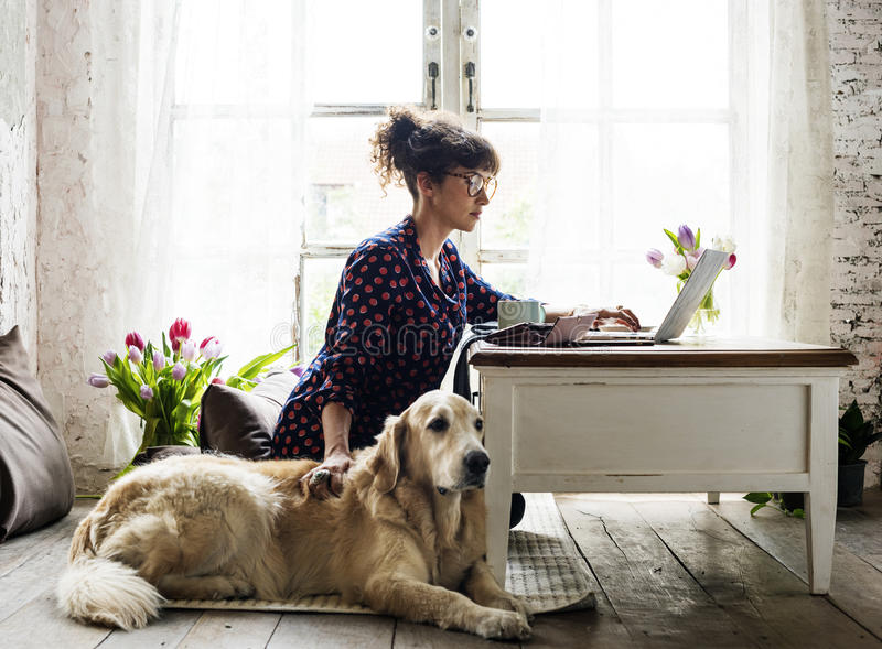 Femme choyant le chien de golden retriever à la maison image libre de droits