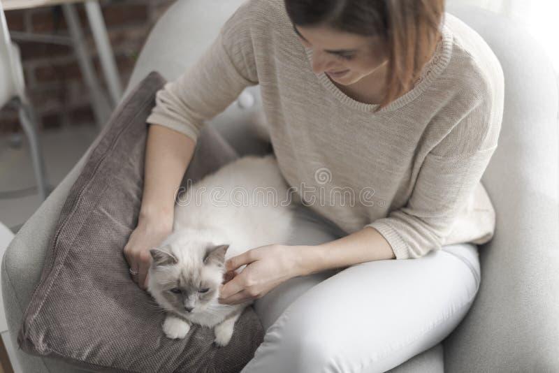 Femme choyant son beau chat à la maison images libres de droits